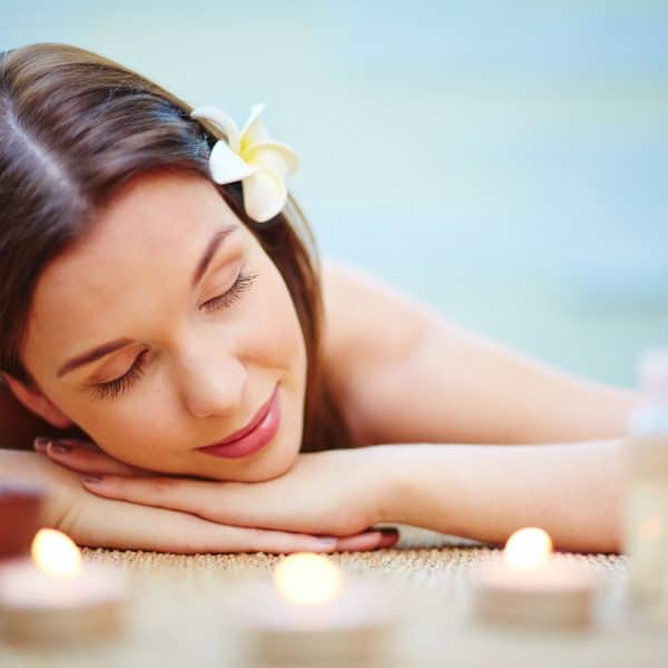 Relaxed female with frangipani flower in hair resting in spa salon