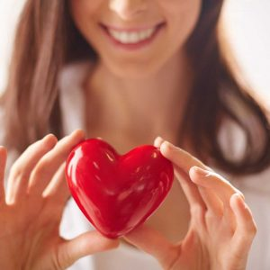 Close-up of smiling female holding red heart